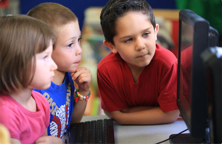 3 students sitting at a computer table looking at computer screen at Prestige Preschool Academy