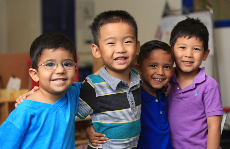 Four Prestige Preschool Academy students smiling while linking arms