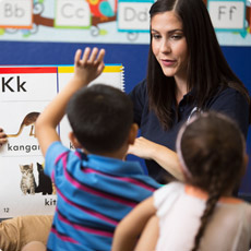 Prestige Preschool Academy teacher reading alphabet pages to children