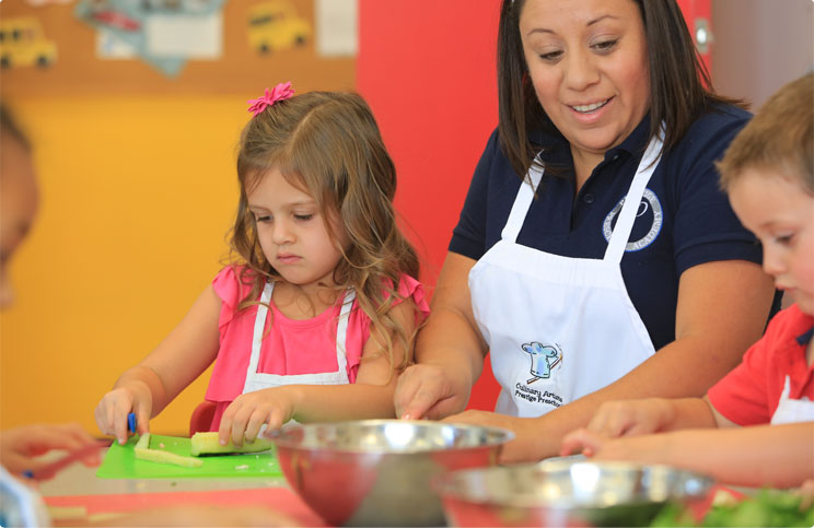 Prestige Preschool academy teacher with 2 students slicing zucchini